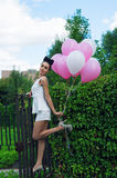 Attractive woman with balloons on the iron gates Royalty Free Stock Photos