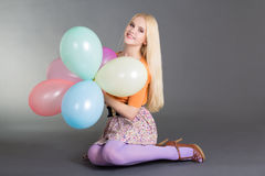 Attractive woman with balloons sitting over grey backgroun Stock Photo