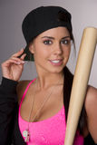 Pretty Female Baseball Lover Adjusts Hat Holding Wooden Bat royalty free stock image