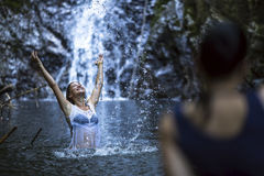 An attractive  woman bathing near the waterfall. Stock Photos