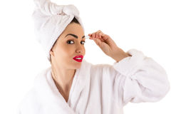 Attractive woman in bathrobe plucks eyebrows Stock Photos