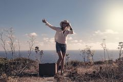 Attractive woman at the beach hitchhiking. An attractive woman at the beach hitchhiking Stock Photo