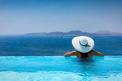Attractive woman  enjoys the view from the pool to the Mediterranean sea. Attractive woman with beautiful hat enjoys the view from the pool to the Mediterranean Royalty Free Stock Photography