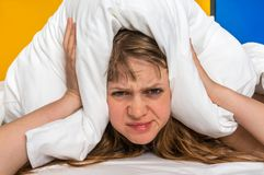 Woman in bed covering ears with pillow because of noise. Attractive woman in bed covering ears with pillow because of noise - insomnia concept royalty free stock image