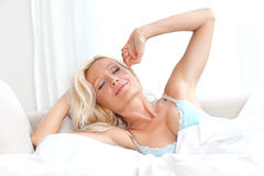 Attractive woman in bed waking up Stock Images