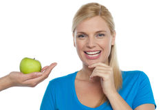 Attractive woman is being offered a green apple Royalty Free Stock Photography