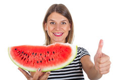 Attractive woman with a big slice of watermelon - thumbs up. Portrait of an attractive woman holding a big slice of watermelon , showing thumbs up on isolated royalty free stock photography