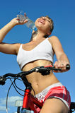 Attractive woman with bike Stock Images