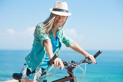Attractive woman with bike. At the sea Stock Photos