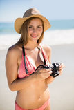 Attractive woman in bikini checking photographs Royalty Free Stock Photos