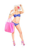 Attractive woman in bikini holding a pink bag Royalty Free Stock Image