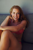 Attractive woman in bikini sitting on couch Royalty Free Stock Image