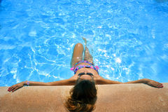 Attractive woman in bikini and sunglasses sunbathing leaning on edge of holidays resort swimming pool Royalty Free Stock Image