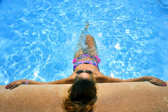 Attractive woman in bikini and sunglasses sunbathing leaning on edge of holidays resort swimming pool. Young attractive woman in bikini and sunglasses sunbathing Royalty Free Stock Photos