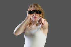 Attractive woman with binoculars and pointing Stock Photos