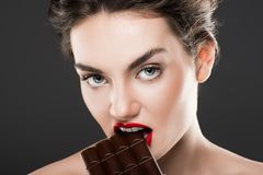 Attractive woman biting chocolate bar. Isolated on grey stock photo