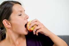 Attractive woman biting a fresh red apple Stock Image
