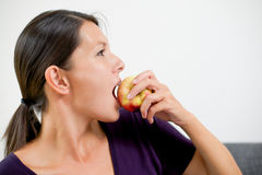 Attractive woman biting a fresh red apple Royalty Free Stock Photo
