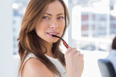 Attractive woman biting her glasses. In modern office royalty free stock photos