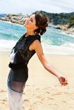 Attractive woman in black dress enjoying sea breeze. Royalty Free Stock Photo