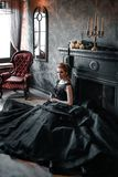 Attractive woman in black dress in medieval interior. Attractive woman in black gothic dress. Indoor shoot royalty free stock image