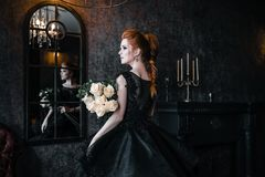 Attractive woman in black dress in medieval interior stock image