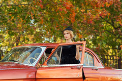 Attractive woman in black dress standing with retro car Stock Images