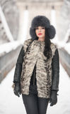 Attractive woman with black fur cap and gray waistcoat enjoying the winter. Frontal view of fashionable brunette girl posing Royalty Free Stock Photo
