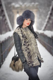 Attractive woman with black fur cap and gray waistcoat enjoying the winter. Frontal view of fashionable brunette girl posing Royalty Free Stock Photos