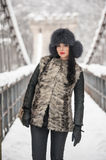 Attractive woman with black fur cap and gray waistcoat enjoying the winter. Frontal view of fashionable brunette girl posing. On a snow covered bridge Stock Image