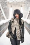 Attractive woman with black fur cap and gray waistcoat enjoying the winter. Frontal view of fashionable brunette girl posing. On a snow covered bridge Royalty Free Stock Photos
