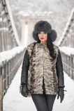 Attractive woman with black fur cap and gray waistcoat enjoying the winter. Frontal view of fashionable brunette girl posing. On a snow covered bridge Royalty Free Stock Photography