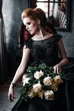 Attractive woman in black dress in medieval interior stock images