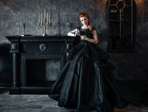 Attractive woman in black dress in medieval interior. Attractive woman in black gothic dress. Indoor shoot stock photos