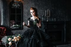 Attractive woman in black dress in medieval interior. Attractive woman in black gothic dress. Indoor shoot royalty free stock images