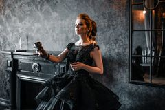 Attractive woman in black dress in medieval interior. Attractive woman in black gothic dress. Indoor shoot royalty free stock photos
