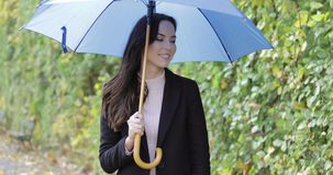 Laughing woman with umbrella. Attractive woman in black jacket holding blue umbrella and happily laughing during her walk in autumn park on rainy day stock video footage