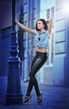 Attractive woman in black leather pants and shirt posing on the street Stock Images