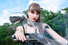 Attractive woman on a black motorbike Royalty Free Stock Photography