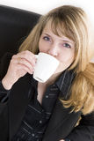 An attractive woman in a black suit drinking a cup of coffee. A blond woman in a black suit drinking a cup of coffee Stock Photo