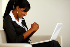 Attractive woman on black suit with a laptop. Portrait of an attractive woman on black suit celebrating a business victory while looking to her laptop and Stock Images