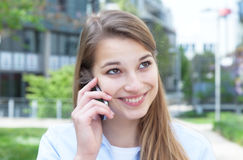 Attractive woman with blond hair laughing at phone Stock Photos