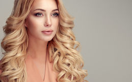 Attractive woman blonde with elegant hairstyle. Close up portrait of attractive blonde woman with elegant and stylish hairstyle. Example of long,dense and curly Royalty Free Stock Images