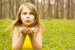 Attractive woman blowing kiss in spring nature. Copy space Royalty Free Stock Image