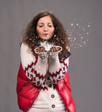 Attractive woman blowing snow. On a gray background Royalty Free Stock Image