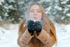 Attractive woman blowing snow in hands. Outdoors Stock Photo