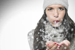 Attractive woman blowing snowflakes Royalty Free Stock Images