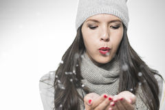 Attractive woman blowing snowflakes Stock Photography