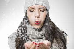Attractive woman blowing snowflakes Royalty Free Stock Image