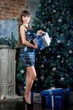 Attractive woman in blue glitter dress in interior. Christmas gift Stock Images